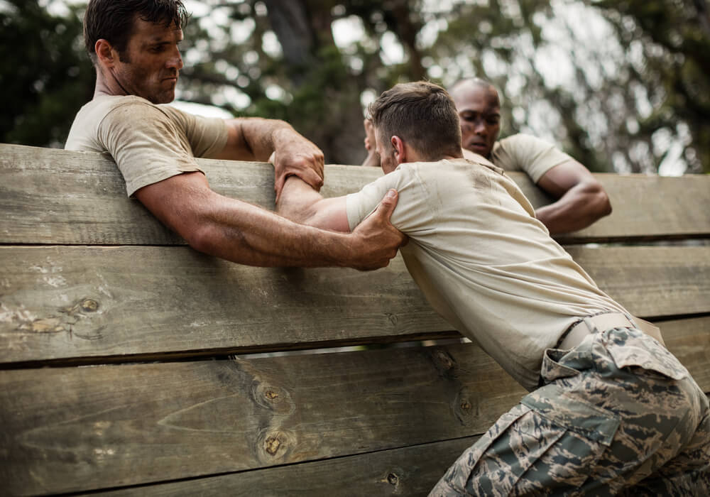 Men dressed in army clothes completing an obstacle course