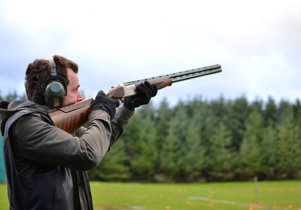 Man trying clay pigeon shooting on stag do