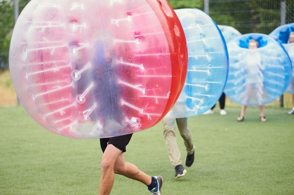 Men playing bubble football on stag weekend