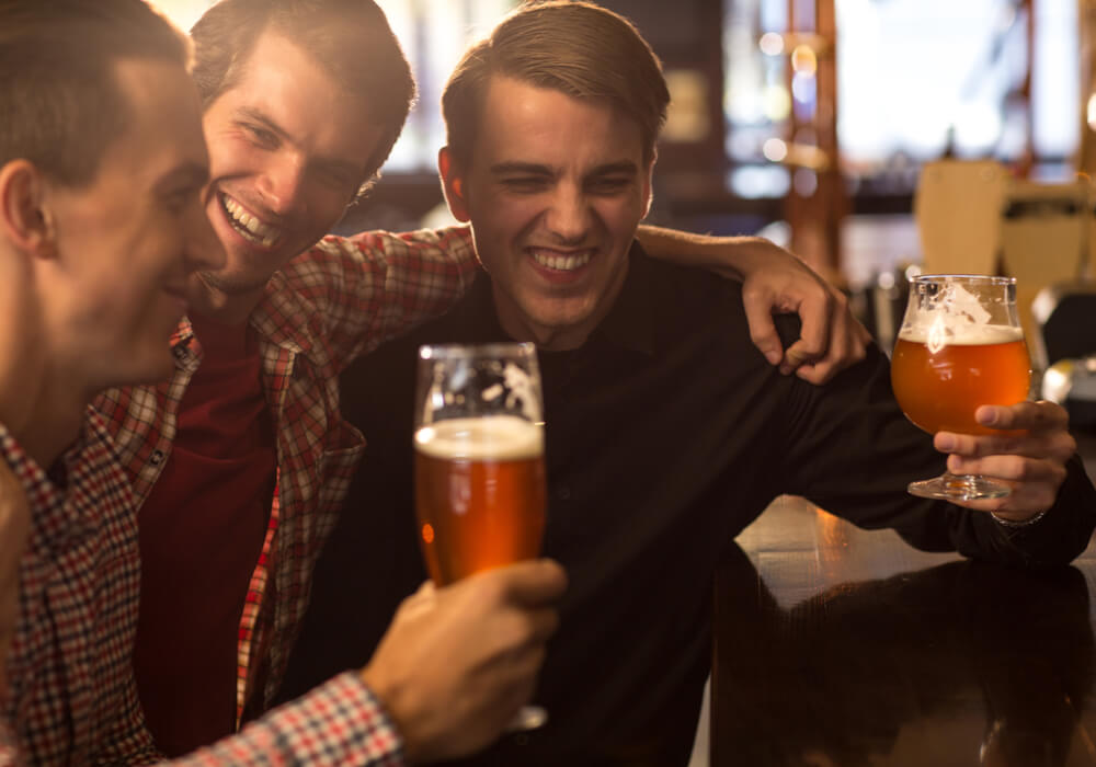 Men at a comedy club enjoying pints of beer