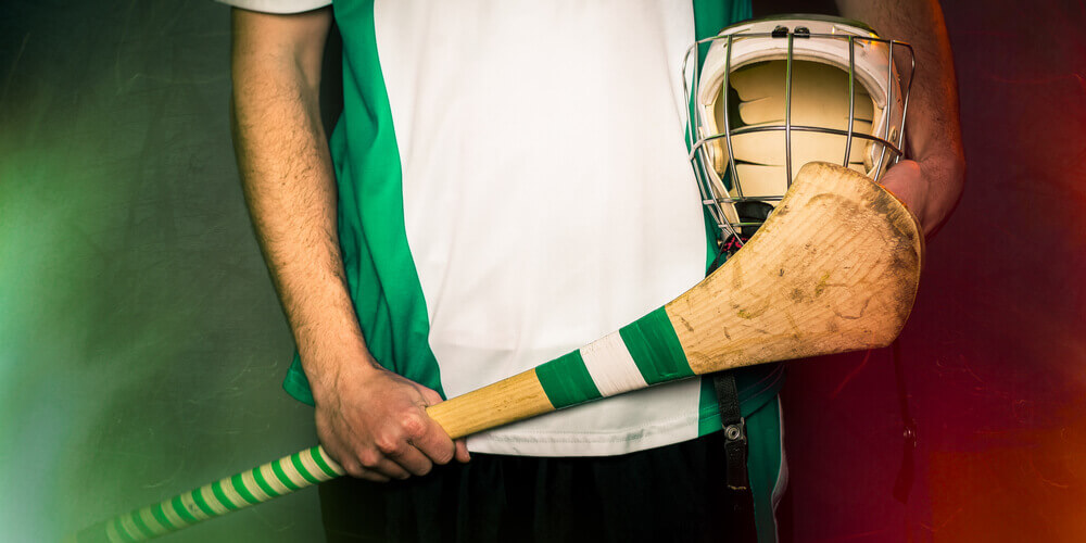 Irish Hurling player's midsection holding hurling stick and helmet