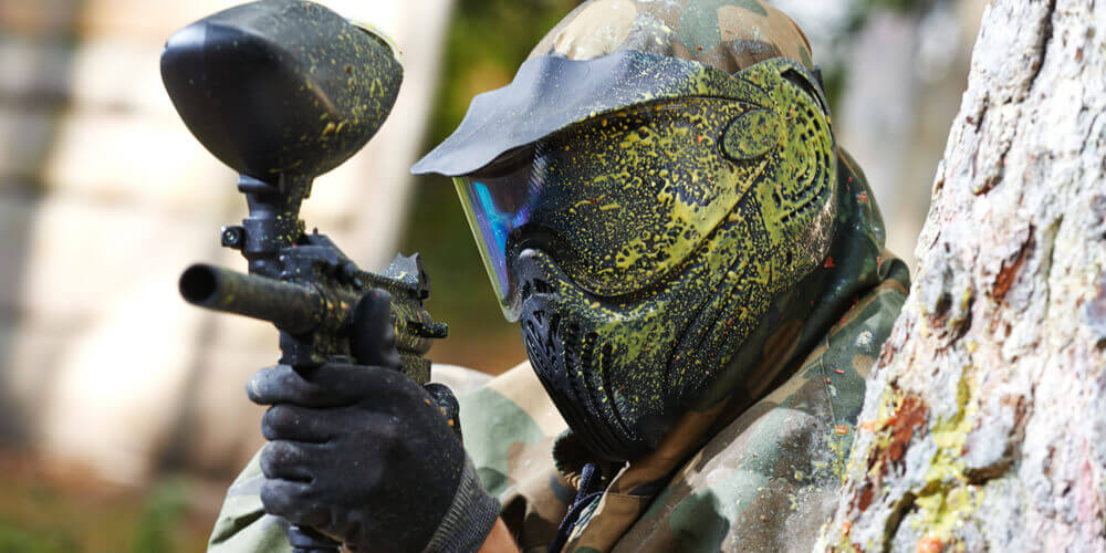 Man hiding behind tree whilst paintballing with yellow paint splattered on his helmet