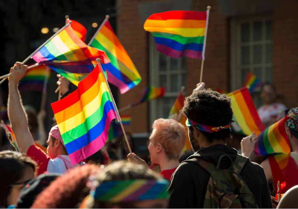 Large crowd celebrating Pride and waving rainbow flags