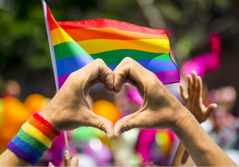 Hands making the shape of a heart with rainbow coloured flags for Pride