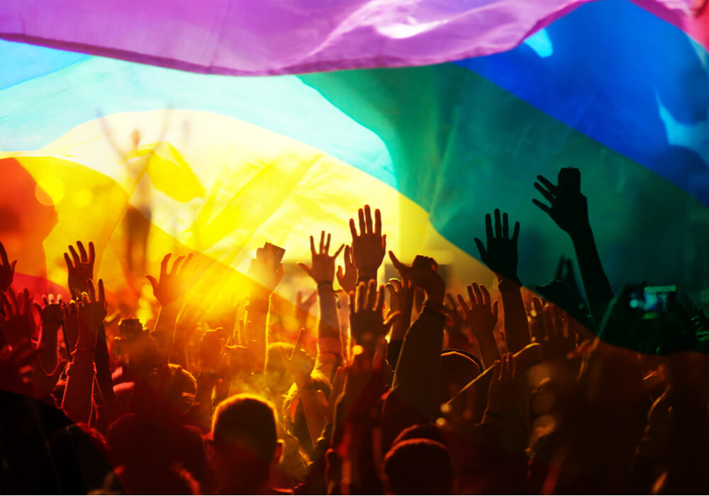 People celebrating Pride with rainbow coloured flag above