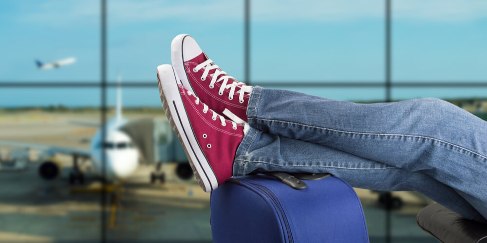 Man waiting for flight with feet up on suitcase and plane in the background
