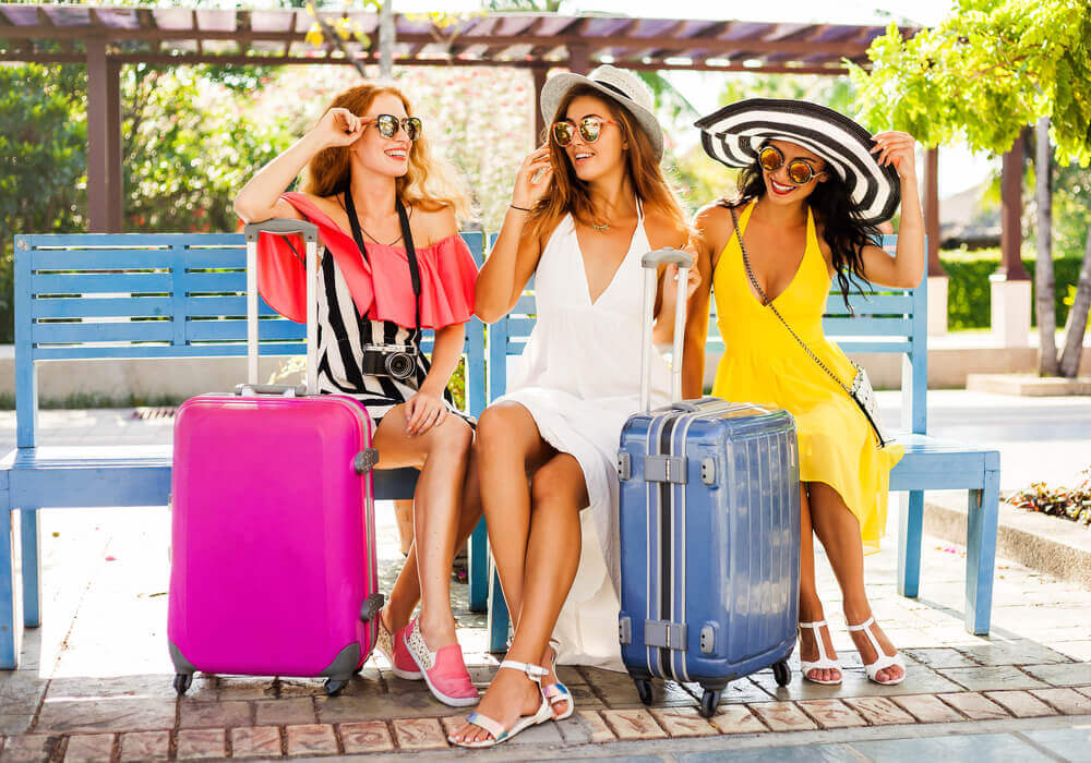 Group of friends going on a hen weekend dressed brightly with luggage