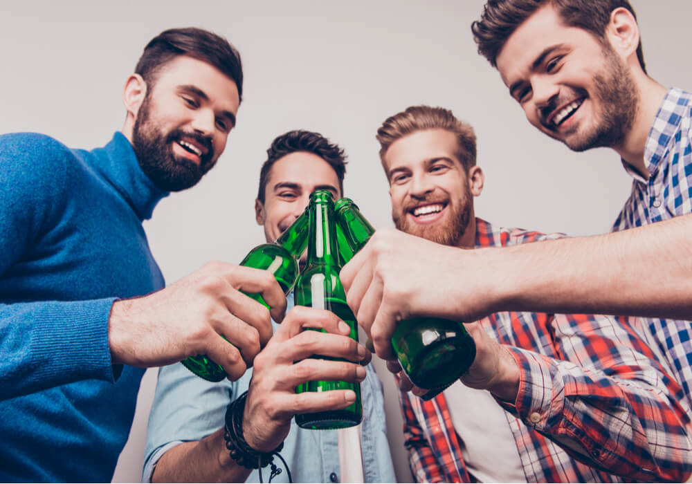 Men celebrating their stag do with bottles of beer