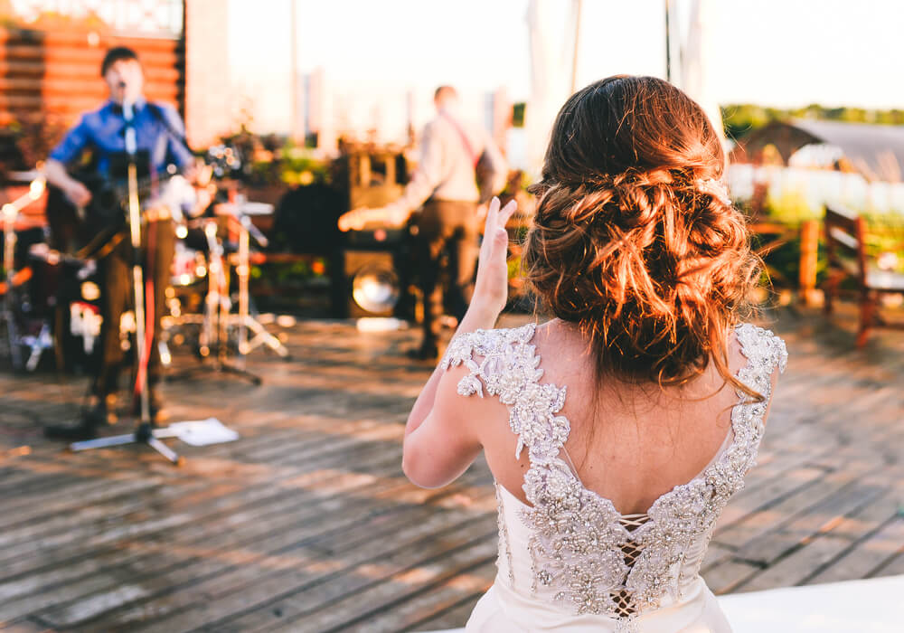 Bride clapping along to wedding band